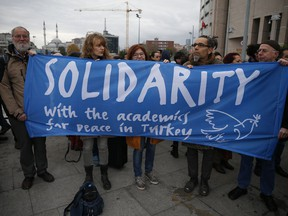 """A delegation of academics and human rights activists from Germany participate in a protest outside a court in Istanbul, Tuesday, Dec. 5, 2017, where Turkish academics went on trial for signing a declaration calling for end of hostilities in Turkey's southeast. The so-called """"Academics for Peace"""", a group of academics from universities in Istanbul, are standing trial on charges of engaging in """"terrorist propaganda"""" for signing a declaration calling for an end of hostilities against Kurdish rebels in Turkey's southeast. Many of the academics lost their jobs."""