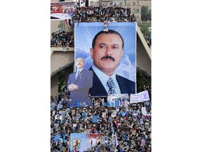 """FILE - In this Aug. 24, 2017 file photo, supporters of former Yemeni President Ali Abdullah Saleh attend a ceremony to celebrate the 35th anniversary of the founding of the Popular Conference Party, in Sanaa, Yemen, Aug. 24, 2017. Yemenis in the war-torn country's capital crowded into basements overnight, Monday Dec. 4, 2017, as Saudi-led fighter jets pounded the positions of Houthi rebels, who are now fighting forces loyal to Saleh for control of the city. A Sanaa-based protection and advocacy adviser for the Norwegian Refugee Council said Monday that the violence left aid workers trapped inside their homes and was """"completely paralyzing humanitarian operations."""""""