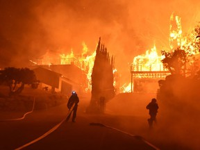 In this photo provided by the Ventura County Fire Department, firefighters work to put out a blaze burning homes early Tuesday, Dec. 5, 2017, in Ventura, Calif. Authorities said the blaze broke out Monday and grew wildly in the hours that followed, consuming vegetation that hasn't burned in decades.