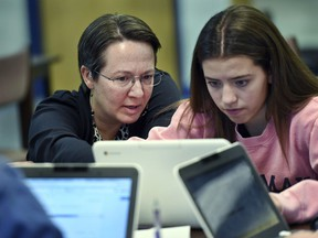 In this, Dec. 20, 2017 photo, Jennifer Rocca, left, a teacher librarian at Brookfield, Conn., High School, left, works with Ariana Mamudi, 14, a freshman in her Digital Student class. The required class teaches media literacy skills and has the students scrutinize sources for their on-line information.