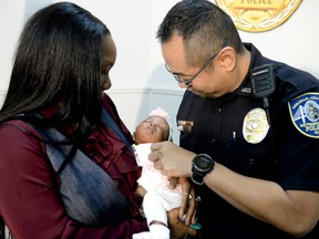 Savannah-Chatham police officer William Eng, right, plays with 29-day-old Bella Adkins while her mother, Tina Adkins, holds her on Monday, Dec. 4, 2017, at Savannah-Chatham police headquarters. Eng performed life-saving CPR on the infant on Friday.