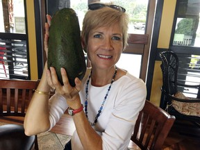 In this Nov. 28, 2017 photo, Pamela Wang poses for a photo in Kealakekua, Hawaii, with an avocado she found while on a walk. Wang is waiting to hear back from Guinness World Records to find out if the 5-pound (2.3-kilogram) avocado she snagged is the world's largest.