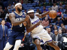 Sacramento Kings forward Zach Randolph, right, drives to the basket against New Orleans Pelicans center DeMarcus Cousins (0) during the first half of an NBA basketball game in New Orleans, Friday, Dec. 8, 2017.
