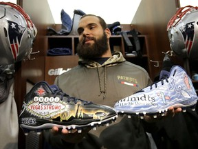 In this Wednesday, Nov. 29, 2017, photo New England Patriots defensive end Lawrence Guy displays cleats that honor victims of the Oct. 2017 Las Vegas shooting, left, and families who have lost an infant, right, in the team's locker room following an NFL football practice, in Foxborough, Mass. Guy will honor both causes on the field this weekend during the NFL's My Cause, My Cleats initiative.