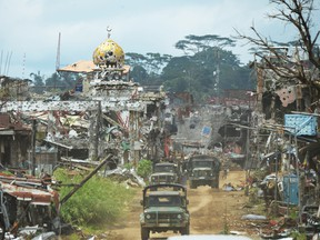Military trucks drive past destroyed buildings and a mosque in what was the main battle area in Marawi on the southern island of Mindanao on Oct. 25, 2017.