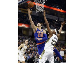 New York Knicks center Enes Kanter (00) shoots under Indiana Pacers center Myles Turner (33) during the first half of an NBA basketball game in Indianapolis, Monday, Dec. 4, 2017.
