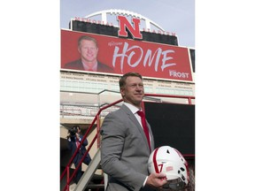 New Nebraska head NCAA college football coach Scott Frost poses at Memorial Stadium with a football helmet following a news conference in Lincoln, Neb., Sunday, Dec. 3, 2017. Frost is returning to Nebraska after orchestrating a stunning two-year turnaround at Central Florida.