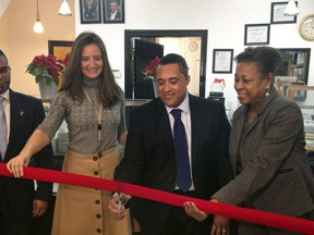Chef Candido Ortiz, center, prepares to cut the ceremonial red ribbon opening his restaurant, El Sabor Del Cafe, Tuesday, Dec. 19, 2017 in Jersey City, N.J. The former prison chef who was serving a 49-year federal sentence for drug-related crimes when he was released in December 2017, is opening a restaurant that will serve American and Hispanic dishes. At left is Edith Palmieri of the New Jersey Re-entry Corporation, and state Sen. Sandra Cunnigham, D-NJ is at right.