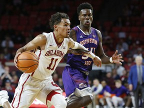 Oklahoma guard Trae Young (11) drives past Northwestern State forward Brandon Hutton, right, in the second half of an NCAA college basketball game in Norman, Okla., Tuesday, Dec. 19, 2017. Oklahoma won 105-68.