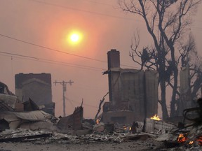 The sun breaks through dense smoke over fire-damaged structures in Ventura, Calif., Tuesday, Dec. 5, 2017. Ferocious Santa Ana winds raking Southern California whipped explosive wildfires Tuesday, prompting evacuation orders for thousands of homes.
