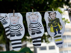 In this March 26, 2017 file photo, a set of inflatable dolls in the likeness of former President Luis Inacio Lula da Silva in prison garb and Judge Sergio Moro as a super hero, hang on a line for sale during a protest against corruption an in support of the Car Wash investigation on Copacabana beach, in Rio de Janeiro, Brazil. Marcelo Odebrecht, one of the most prominent people convicted in Latin America's largest corruption scandal left prison Tuesday, Dec. 19, for house arrest after serving two-and-a-half years behind bars at a time when many Brazilians are becoming disillusioned with the graft investigation once hailed as a political game-changer.