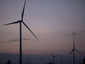 Wind turbines stand at the Subplu wind farm at dusk in Huay Bong, Thailand. MUST CREDIT: Bloomberg photo by Brent Lewin