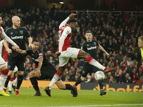 Arsenal's Danny Welbeck, centre, scores the opening goal of the game during the English League Cup quarterfinal soccer match between Arsenal and West Ham United at the Emirates stadium in London, Tuesday, Dec. 19, 2017.