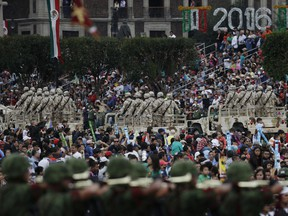FILE - In this Sept. 16, 2016 file photo, people watch soldiers during the annual Independence Day military parade in Mexico City's main square, known as the Zocalo. Mexico's National Human Rights Commission denounced on Dec. 5, 2017 a case of alleged abuses in 2016 by members of the military, which is heavily involved in prosecuting the country's war against drug gangs.