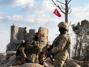 Pro-Turkey Syrian fighters and Turkish troops secure the Bursayah hill, which separates the Kurdish-held enclave of Afrin from the Turkey-controlled town of Azaz, Syria, in a photo taken Jan. 28, 2018.