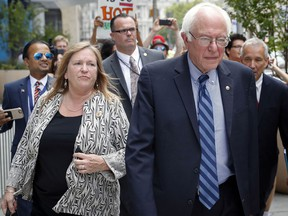 FILE - In this July 28, 2016, file photo, Sen. Bernie Sanders, I-Vt. and his wife Jane walk through downtown in Philadelphia during the final day of the Democratic National Convention. A former Burlington College trustee said she testified before a grand jury in October 2016, about a fundraising deal that was undertaken while Jane Sanders was president of the now-defunct Vermont school.