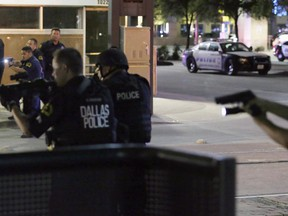 FILE - In this July 7, 2016, file photo, Dallas police move to detain a driver after several police officers were shot in downtown Dallas when a sniper opened fire at a Black Lives Matter protest. A grand jury on Wednesday, Jan. 31, 2018, declined to bring charges against Dallas police officers responsible for the death of the sniper.