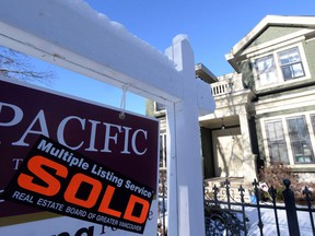 """A real estate sold sign is shown outside a house in Vancouver, Tuesday, Jan.3, 2017. The Real Estate Board of Greater Vancouver says home sales across Metro Vancouver were steady but more """"historically normal"""" in 2017, although prices continued to climb."""