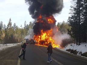 In this photo provided by Steve Corso people watch as flame rise from a deadly crash between a pickup and a fuel tanker Wednesday, Jan. 31, 2018, that shut down a stretch of U.S. Highway 20 west of Truckee, Calif. California Highway Patrol Officer Chris Nave said both drivers were killed in the crash that caused the tanker to explode shortly after 10 a.m. Wednesday.