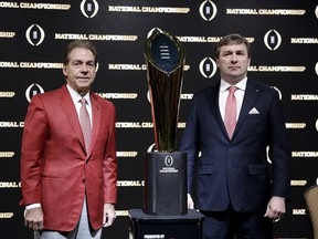 Alabama head coach Nick Saban, left, and Georgia head coach Kirby Smart pose with the NCAA college football championship trophy at a press conference in Atlanta, Sunday, Jan. 7, 2018. Georgia and Alabama will be playing for the championship on Monday, Jan. 8.