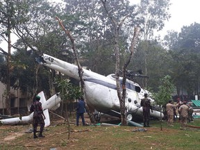 In this Wednesday, Jan. 3, 2018, photo released by Kuwait News Agency, KUNA, Bangladeshi authorities check the site of a helicopter crash in Moulvibazar district, northeastern Bangladesh which was carrying Kuwait's chief of staff Lieutenant General Mohammed Khaled Al-Khadher, who survived. (KUNA via AP)