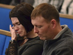 A woman wipes tears from her eye during a prayer vigil at Briensburg Baptist Church near Benton, Ky., Tuesday, Jan. 23, 2018. Bailey Nicole Holt and Preston Ryan Cope, both 15, were killed and another 17 people injured when a classmate opened fire Tuesday morning in the Marshall County High School atrium, a common area at the school where several hallways meet and students gather before classes.
