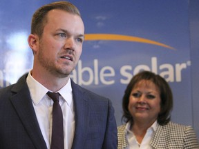 File- This Feb. 1, 2017, file photo shows Affordable Solar president Kevin Bassalleck talking about the full-time positions his company will create as Gov. Susana Martinez listens during a news conference in Albuquerque, N.M. Some in the U.S. solar-power industry are hoping a decision this week by President Donald Trump doesn't bring on an eclipse. Companies that install solar-power systems for homeowners and utilities are bracing for Trump's call on whether to slap tariffs on imported panels. Bassalleck, said tariffs would hurt homegrown companies that make racks, tracking systems and electronics that are part of a power system. He said jobs at those companies are hard to outsource.