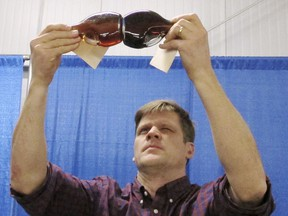In this Monday, Jan. 29, 2018 photo, Mark Isselhardt, a University of Vermont extension maple specialist, studies the color of maple syrup entries in an annual contest at the Vermont Farm Show in Essex Junction, Vt. Vermont is the country's largest producer of maple syrup.