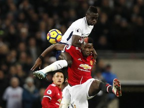 Manchester United's Paul Pogba jumps for the ball with Tottenham's Davinson Sanchez, top, during the English Premier League soccer match between Tottenham Hotspur and Manchester United at Wembley stadium in London, England, Wednesday, Jan. 31, 2018.