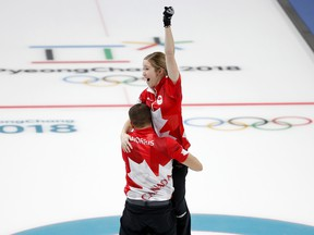 Canada's Kaitlyn Lawes and John Morris celebrate their gold medal in mixed doubles curling at the Pyeongchang Olympics on Feb. 13.