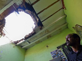 A picture taken March 26, 2018 in Um Al-Hammam district in Riyadh shows a man looking at a hole in a household ceiling caused by falling shrapnel from Yemeni rebel missiles that were reported to have been intercepted over the Saudi capital.