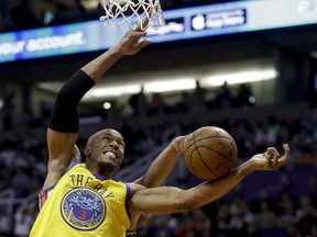 Golden State Warriors forward David West, front, and Phoenix Suns forward Jared Dudley reach for a loose ball during the first half of an NBA basketball game in Phoenix, Saturday, March 17, 2018.