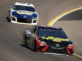 Monster Energy NASCAR Cup Series driver Martin Truex Jr. (78) leads Chase Elliott on the 25th lap during a NASCAR Cup Series auto race on Sunday, March 11, 2018, in Avondale, Ariz.