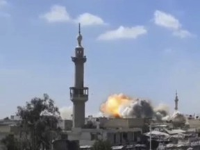 This frame grab from video provided by Syrian rebels Army of Islam media outlet that is consistent with independent AP reporting, shows flames rising from a Syrian government forces airstrike attack, in eastern Ghouta, suburb of Damascus, Syria, Friday, March 9, 2018. Relief workers used a brief lull in Damascus' embattled rebel-held suburbs to try and deliver remaining aid left over from a mission earlier in the week but were interrupted by renewed violence shorty after their team entered eastern Ghouta on Friday.(Army of Islam, via AP)