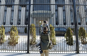A news photographer takes pictures outside the Embassy of the Russian Federation to Canada in Ottawa on Monday, March 26, 2018.
