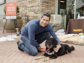"""Arie Luyendyk Jr., star of ABC's """"The Bachelor,"""" cuddles with his dog Bastian in Phoenix, Ariz., on Friday, Feb. 16, 2018. The reality dating series """"The Bachelor"""" hit its 16th anniversary on Sunday and, despite a rocky past year and poor track record of diversity and lasting love connections, its rose petals show no signs of wilting. THE CANADIAN PRESS/AP-Mark Peterman/AP Images for PetSmart Charities)"""