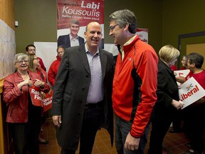 Nova Scotia Liberal Leader Stephen McNeil, right, chats with Labi Kousoulis, in Halifax on Monday, Oct. 7, 2013. Nova Scotia employers would have to provide up to 16 continuous weeks of unpaid leave for employees who are victims of domestic violence under proposed legislation.