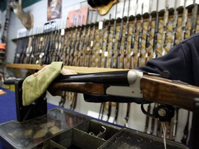 The Liberal government is planning to introduce long-promised legislation as early as Tuesday to strengthen controls on the sale, licensing and tracing of guns. An Ottawa hunting store salesperson wipes a shotgun on Tuesday, May 16, 2006.