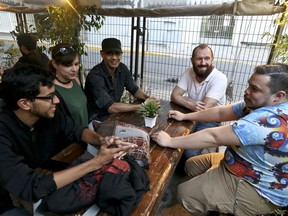 In this March 20, 2018 photo, Guido Nunez-Mujica, right, meets for the firs time with fellow Venezuelans who he helped leave Venezuela, Daniel Klie, left, and Elias Martinez, third from left, as Elias' girlfriend Elizabeth Vieria and Nunez-Mujica' American husband Tom Japhet join them at a bar in Santiago, Chile. Nunez-Mujica, who works in the U.S., is helping resettle a group of young Venezuelans trying to retrace his own immigrant's journey to a better future.