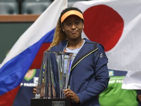 Naomi Osaka, of Japan, poses with her trophy after defeating Daria Kasatkina, of Russia, in the women's final at the BNP Paribas Open tennis tournament, Sunday, March 18, 2018, in Indian Wells, Calif. Osaka won 6-3, 6-2.