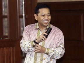 Former speaker of Indonesia's parliament Setya Novanto, center, smiles as he enters the court room after a break during his hearing at the Corruption Cases Court in Jakarta, Indonesia, Thursday, March 29, 2018. The top Indonesian politician was accused of involvement in a conspiracy of dozens of officials who used the introduction of an electronic ID system to steal more than $170 million of public money.