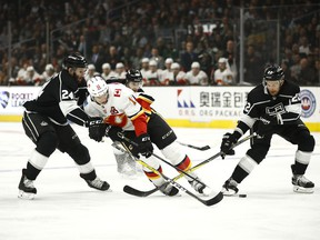 Calgary Flames' Mikael Backlund, center, of Sweden, is defended by Los Angeles Kings' Derek Forbort, left, and Trevor Lewis during the first period of an NHL hockey game Monday, March 26, 2018, in Los Angeles.