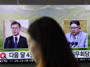 A visitor walks by a TV screen showing file footages of South Korean President Moon Jae-in, left, and North Korean leader Kim Jong Un, right, during a news program at the Seoul Railway Station in Seoul, South Korea, Thursday, March 29, 2018. North Korean leader Kim will meet South Korean President Moon at a border village on April 27, the South announced Thursday after the nations agreed on a rare summit that could prove significant in global efforts to resolve a decades-long standoff over the North's nuclear program.