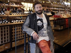 In this photo taken on Friday, March 16, 2018, Russian entrepreneur Yevgeny Chichvarkin poses for a photograph in his wine shop Hedonism, in London. Amid the rising diplomatic tensions, some Russians feel they themselves trapped between stereotypes and political outrage. Chichvarkin, a one-time mobile phone entrepreneur and Kremlin critic who has lived in London for a decade, says he feels a bit less welcome. Even though he runs a an exclusive wine shop in the tony Mayfair district, plans for a new project that will create 200 jobs and contributes to art and society, his neighbors recently rejected his offer to install a trampoline in the local park.