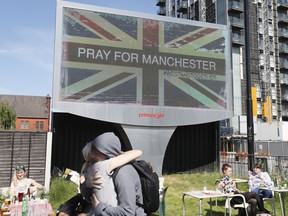 FILE - In this Tuesday May 23, 2017 file photo, couple embrace under a billboard in Manchester, England, the day after the suicide attack at an Ariana Grande concert that left more than 20 people dead. Firefighters were not allowed to go to the scene of the Manchester Arena bombing for more than two hours because of confusion about whether an attacker was still on the loose, according to an inquiry into the attack released Tuesday March 27, 2018.