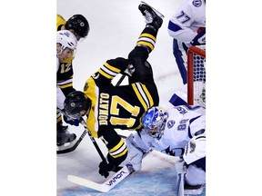 Boston Bruins center Ryan Donato (17) is upended as he collides with Tampa Bay Lightning goaltender Andrei Vasilevskiy (88) during the first period of an NHL hockey game in Boston, Thursday, March 29, 2018.