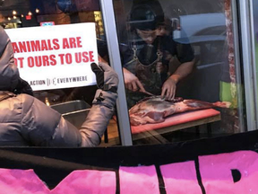 Chef Michael Hunter carves up a deer leg in the window of Toronto's Antler restaurant as  animal rights activists protest outside.