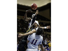 Graceland guard LT Davis, middle, has the ball knocked away by LSU Alexandria forward Brandon Moss, top, as Chris Vickers, bottom, also defends during the first half of the NAIA men's championship college basketball game Tuesday, March 20, 2018, in Kansas City, Mo.