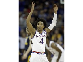Kansas guard Devonte' Graham (4) encourages fans during the first half of an NCAA college basketball game against West Virginia in the finals of the Big 12 men's tournament in Kansas City, Mo., Saturday, March 10, 2018.