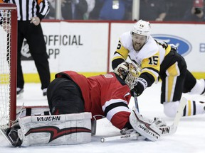New Jersey Devils goaltender Keith Kinkai, front, reaches for the puck next to Pittsburgh Penguins center Riley Sheahan (15) during the first period of an NHL hockey game Thursday, March 29, 2018, in Newark, N.J.